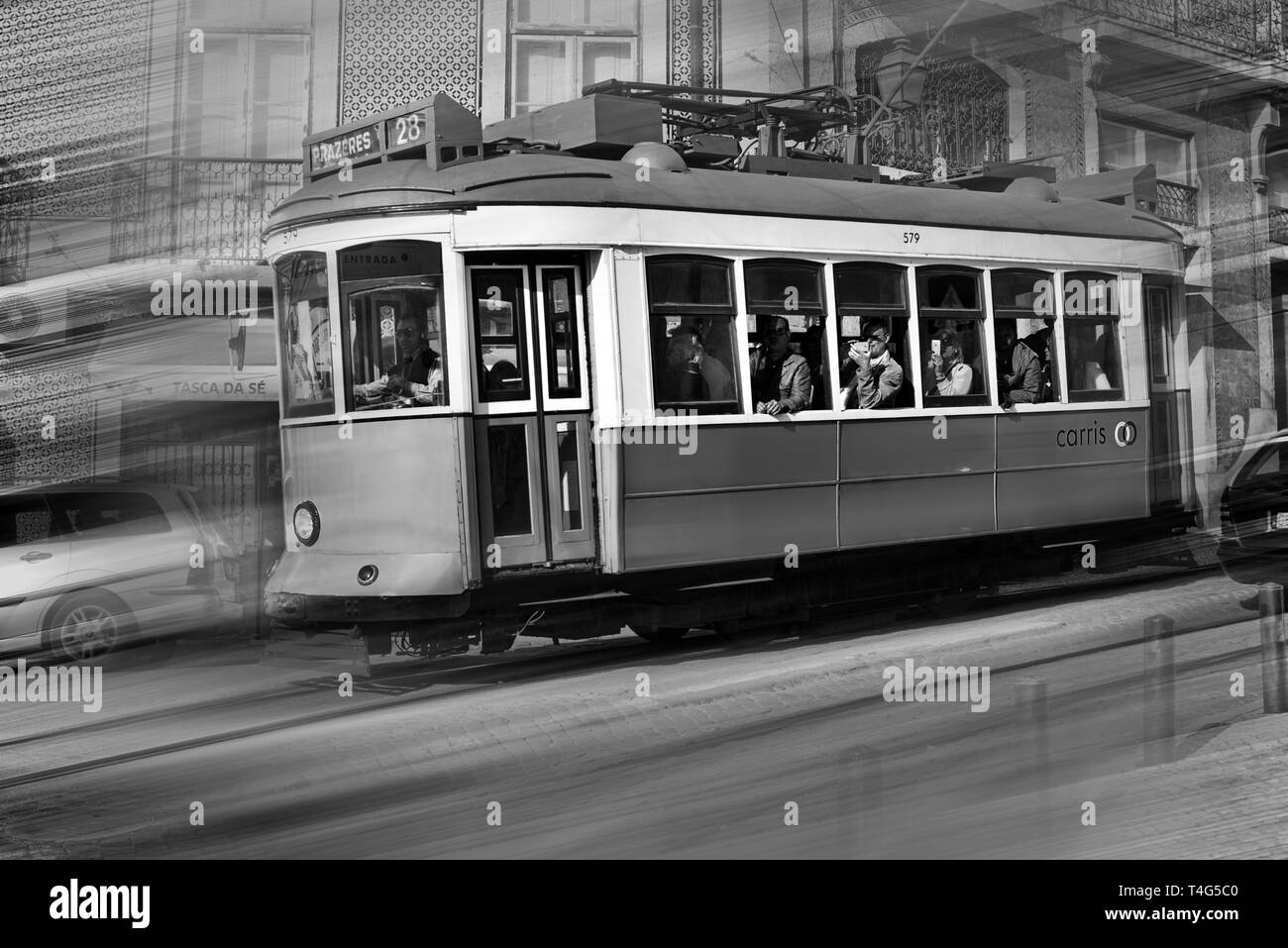 Portugal, Lisbon, Alfama, tram, tramway No. 28, famous, sightseeing, movement, tram in movement, people, passengers, no model releases, travel, tourism, portuguese capital, black and white, black and white photography, nostalgia, nostalgic, charming, stree   usage worldwide - Stock Image