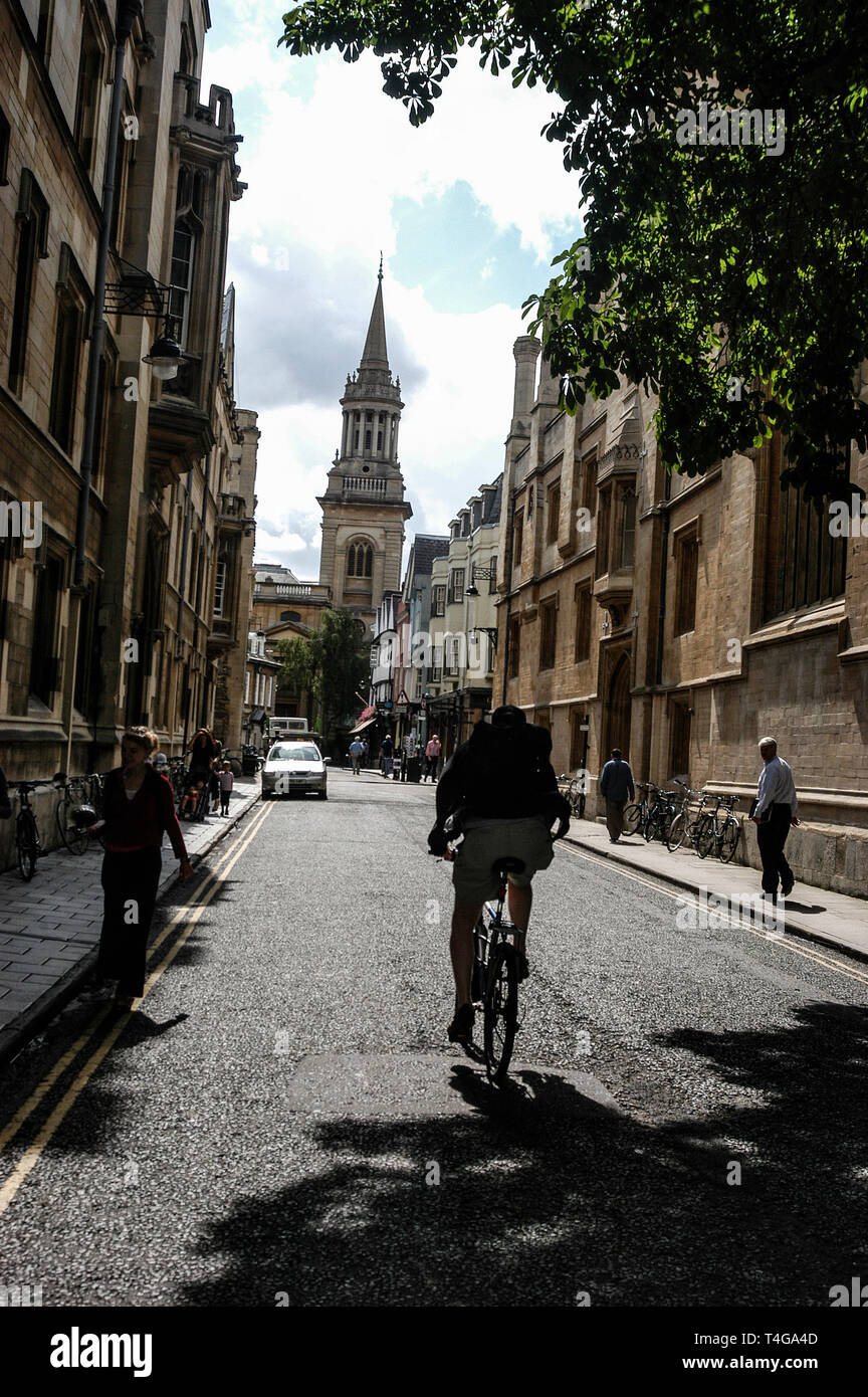 An Oxford student cycling along Turl Street, between Exeter College on left and Jesus College on right.   At the far end of Turl Street is the Church  - Stock Image