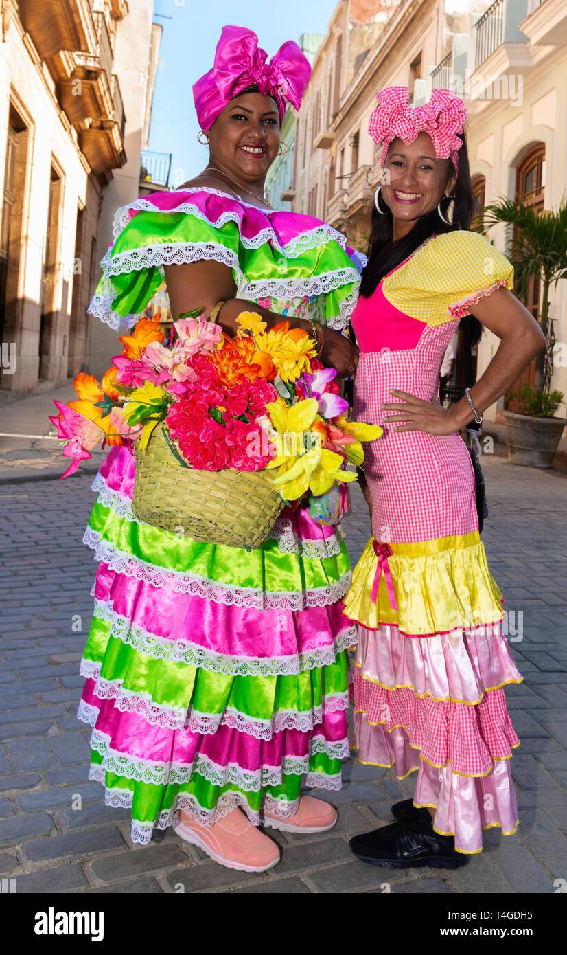 Cuban women with traditional floral  clothing posing for tourists in street in  Old Havana, Cuba Stock Photo