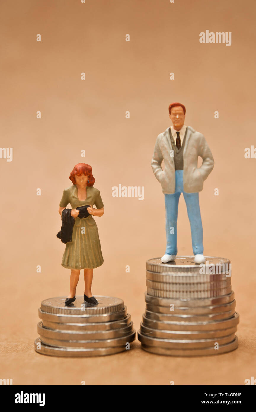 man and woman figurine standing on coins, gender pay gap concept - Stock Image