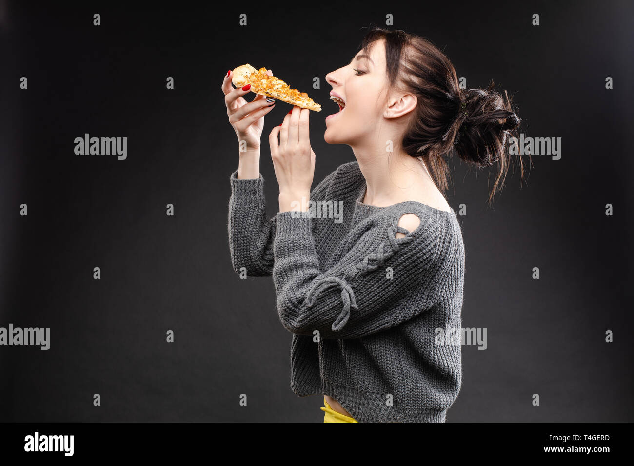 Hungry girl with opened mouth eating pizza - Stock Image