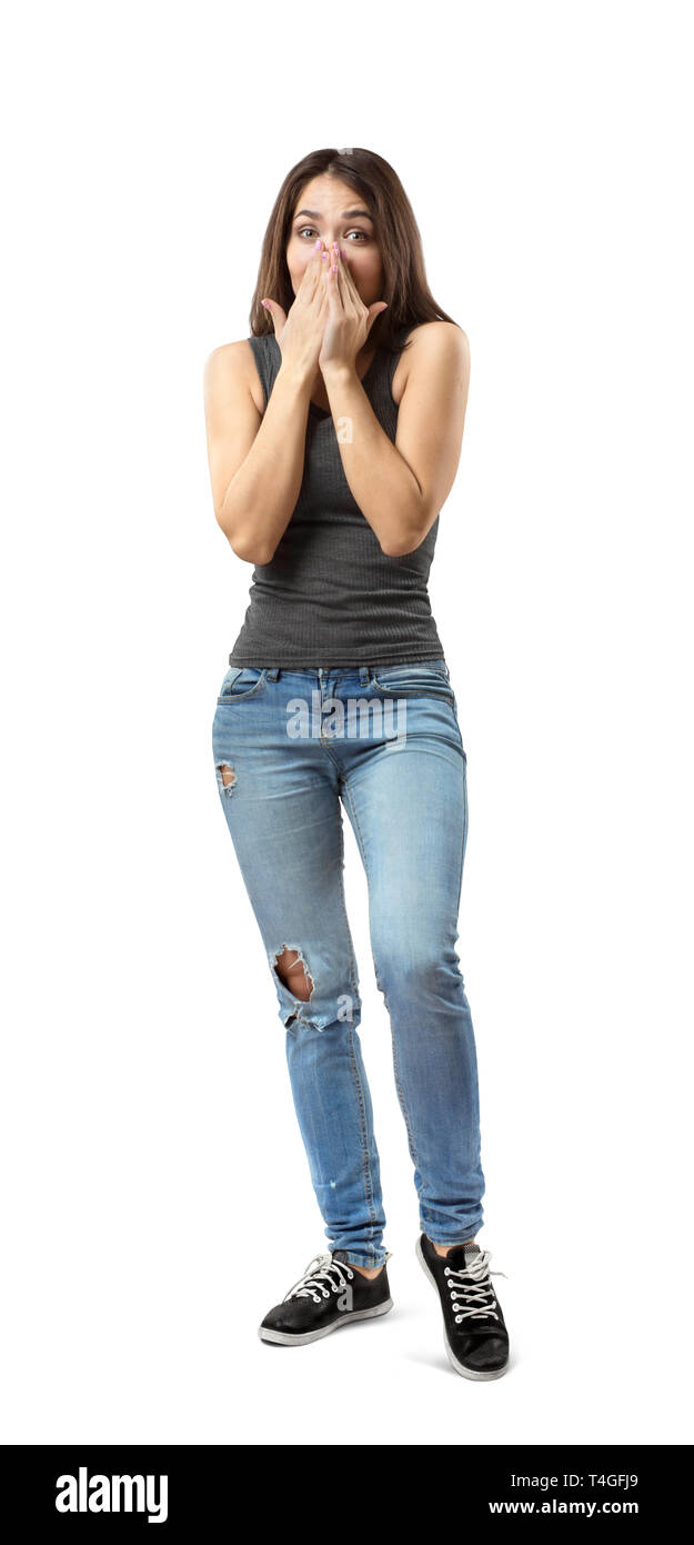 Young woman in gray top and blue jeans covering mouth and nose with her hands, weight on right foot, left knee lifted a bit, isolated on white - Stock Image