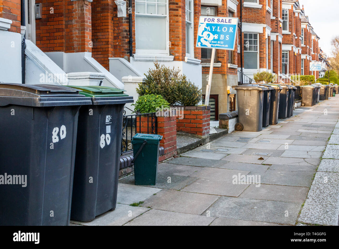 Plastic recycling and refuse wheelie-bins, often obstructing the pavement, awaiting collection by Haringey Council, North London, UK - Stock Image