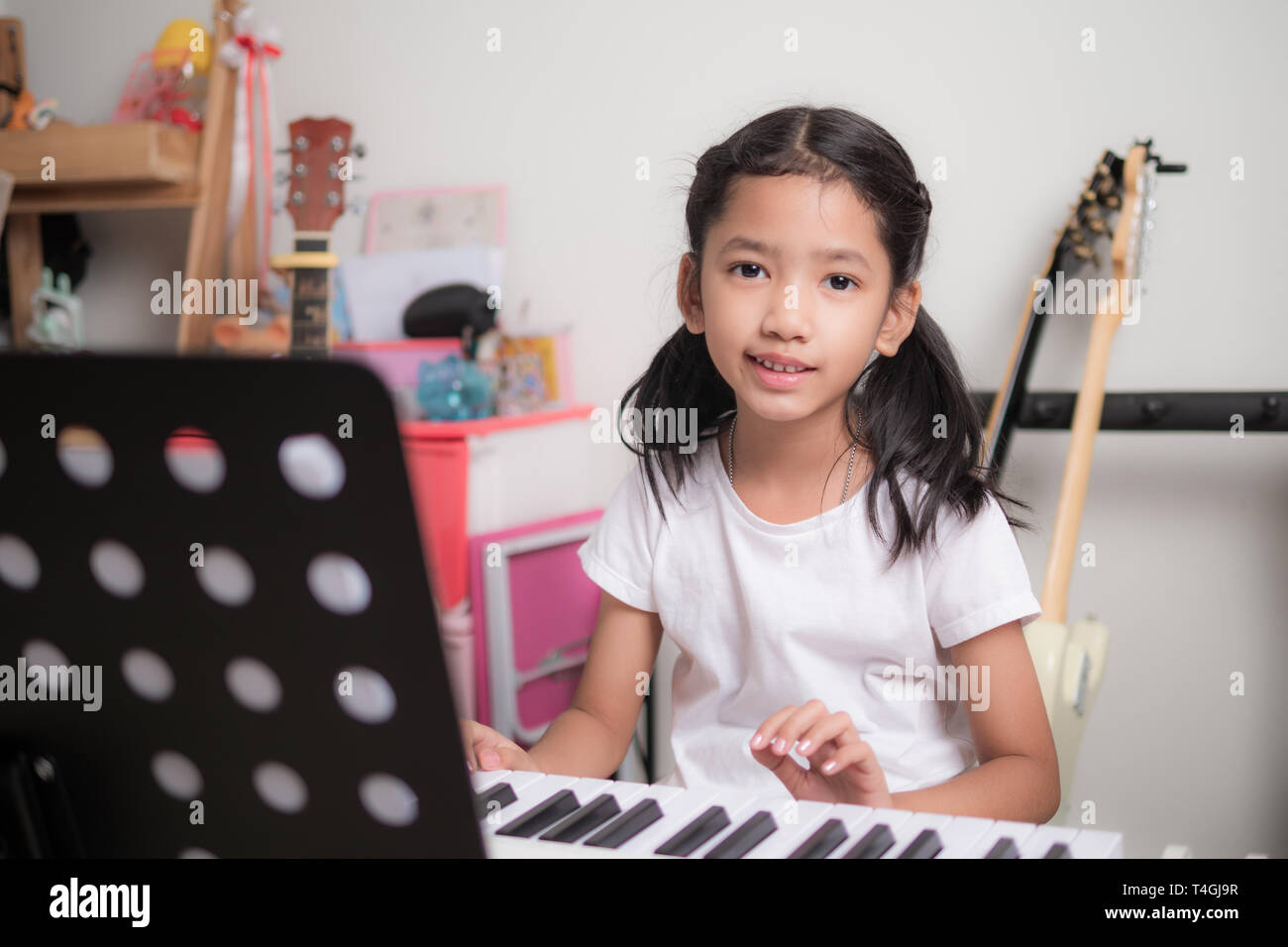 Asian little girl learning to play piano keyboard synthesizer and smile with happiness, Thai girl studying the music at home - Stock Image