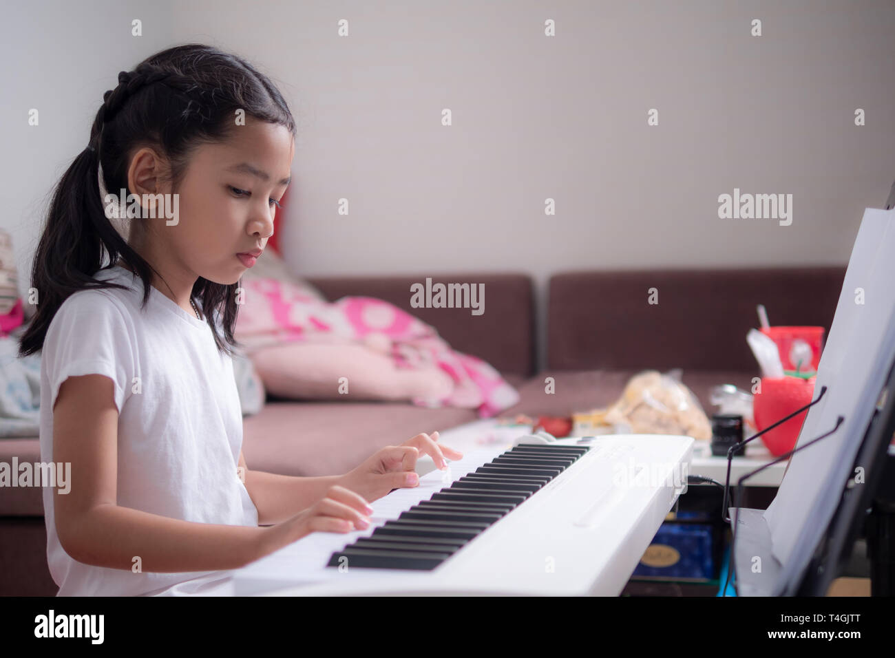 Asian little girl learning to play piano keyboard synthesizer with happiness, Thai girl studying the music at hom - Stock Image