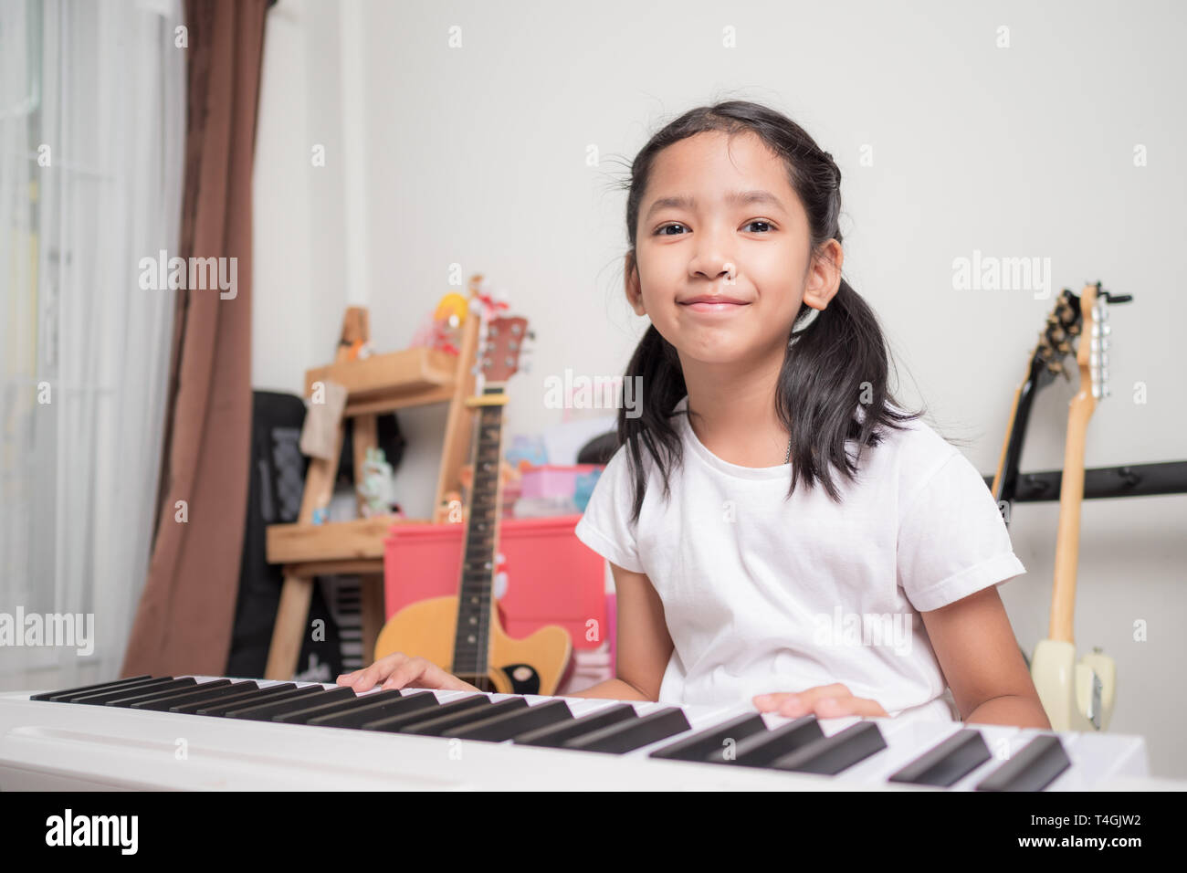 Asian little girl learning to play piano keyboard synthesizer with happiness, Thai girl studying the music at home - Stock Image
