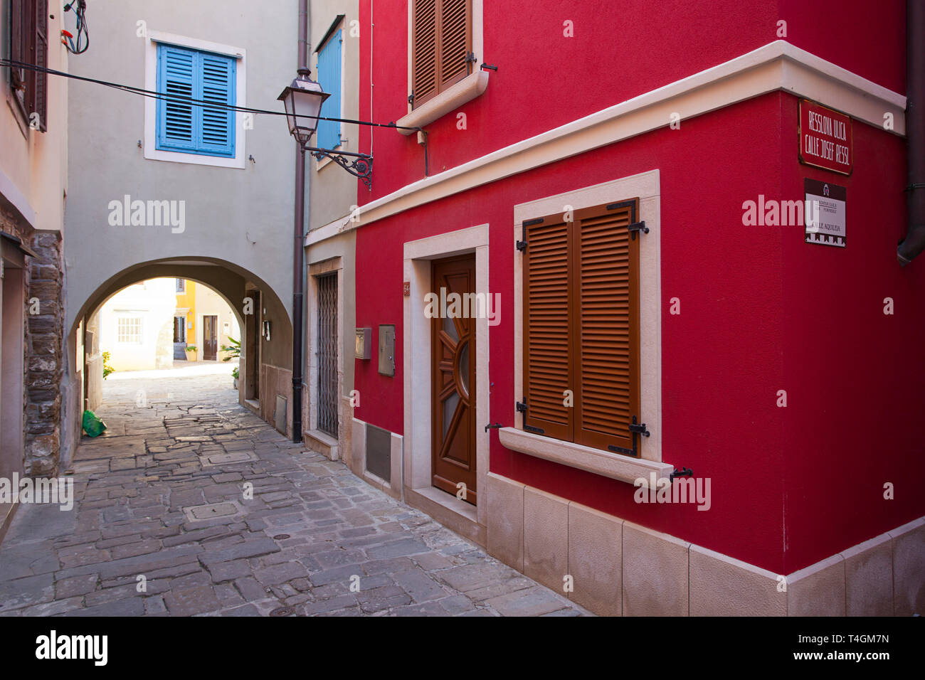 Empty cobbled street and red building - Stock Image
