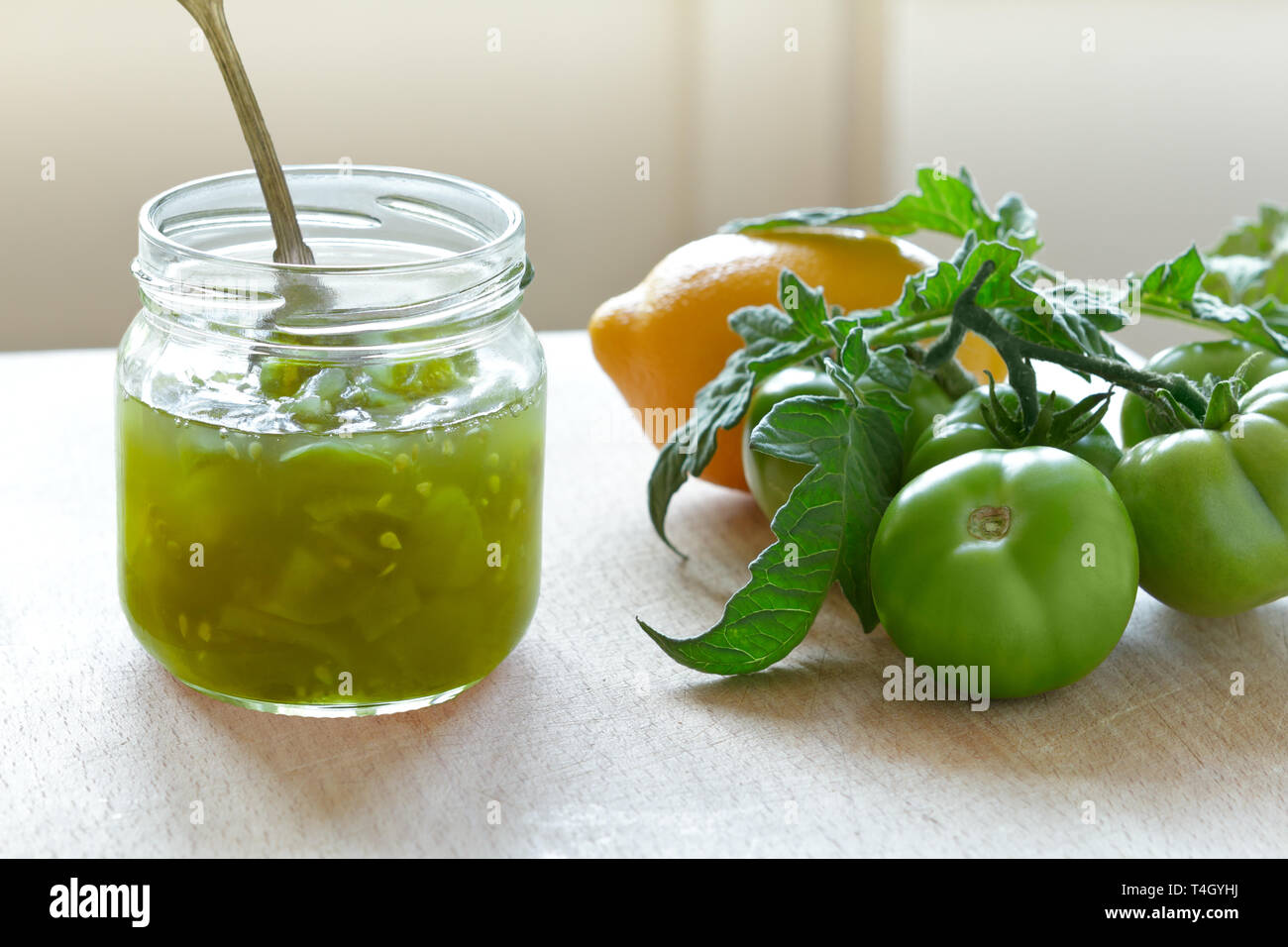 Green tomato jam or chutney in a glass jar with lemon flavoring, home canning concept Stock Photo