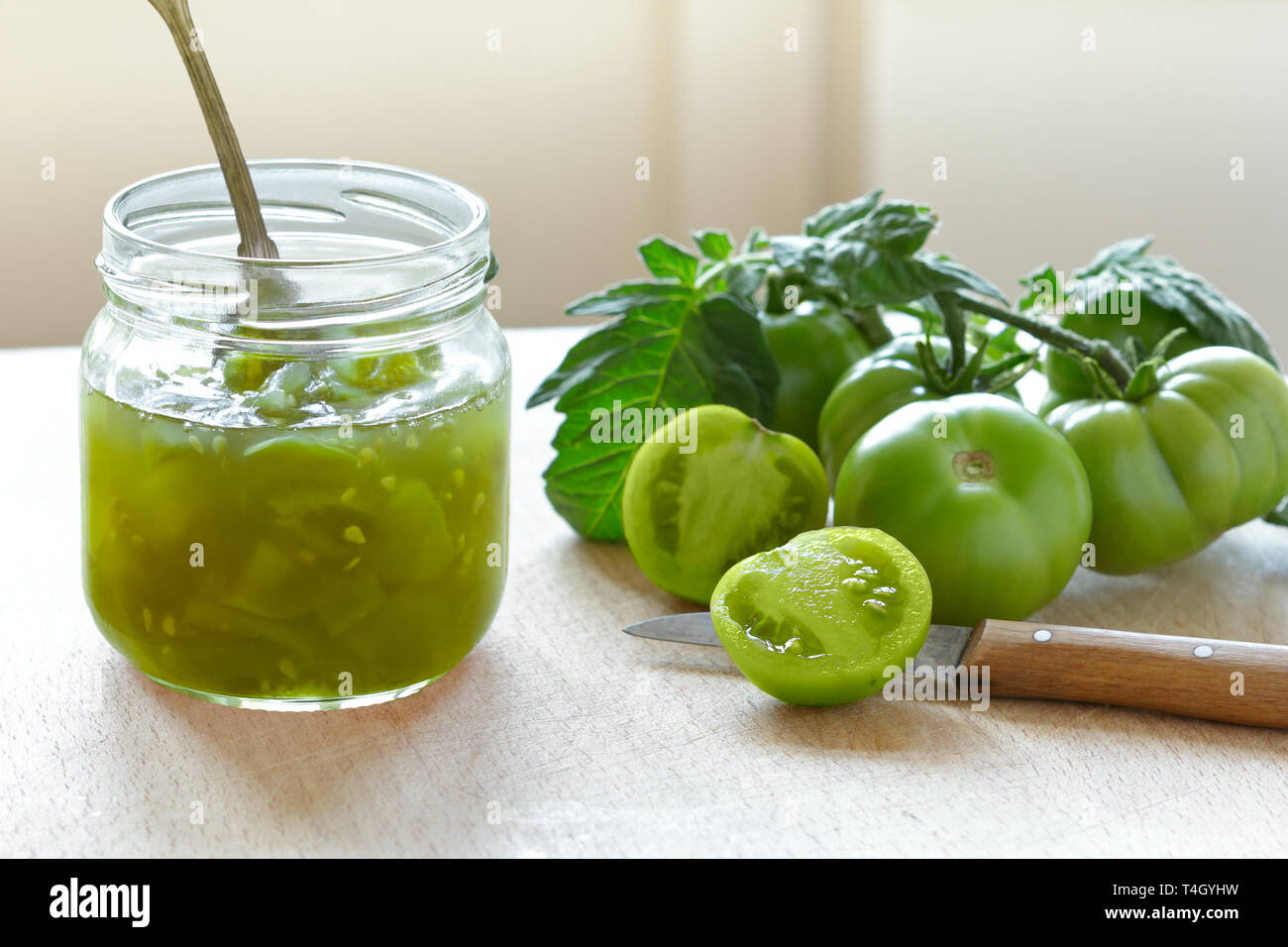 Green tomato jam or chutney in a glass jar with vintage spoon, home canning concept Stock Photo