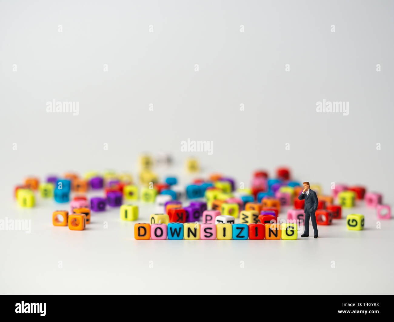 miniature figure businessman in dark blue suit standing backside of colorful of downsizing alphabet and thinking abount how to Reduce trade, spend and - Stock Image