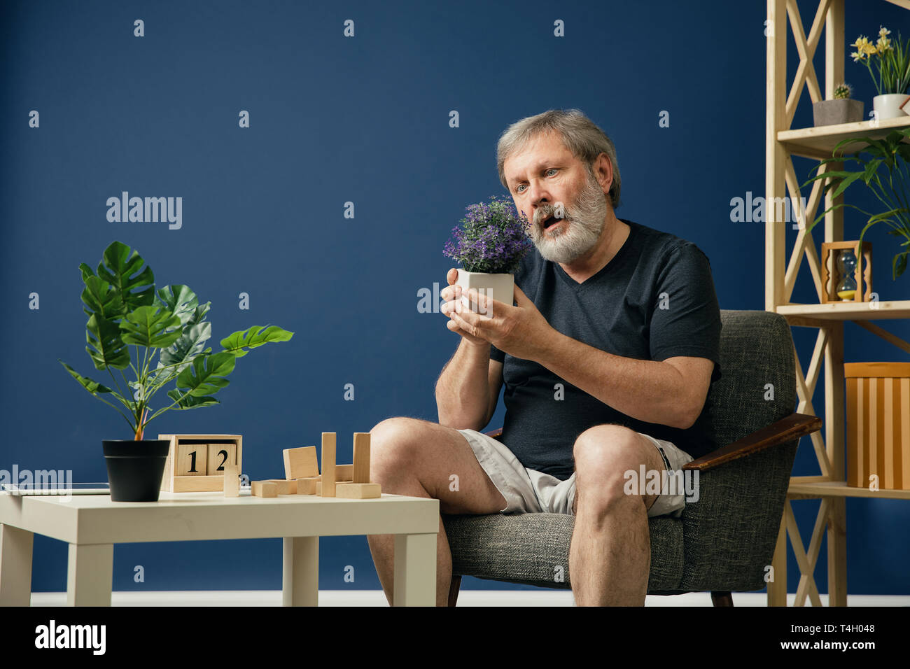 Trying to find happieness. Old bearded man with alzheimer desease has problems with his hands motor skills. Concept of illness, memory loss due to dementia, healthcare, neurological disorder, sadness. - Stock Image