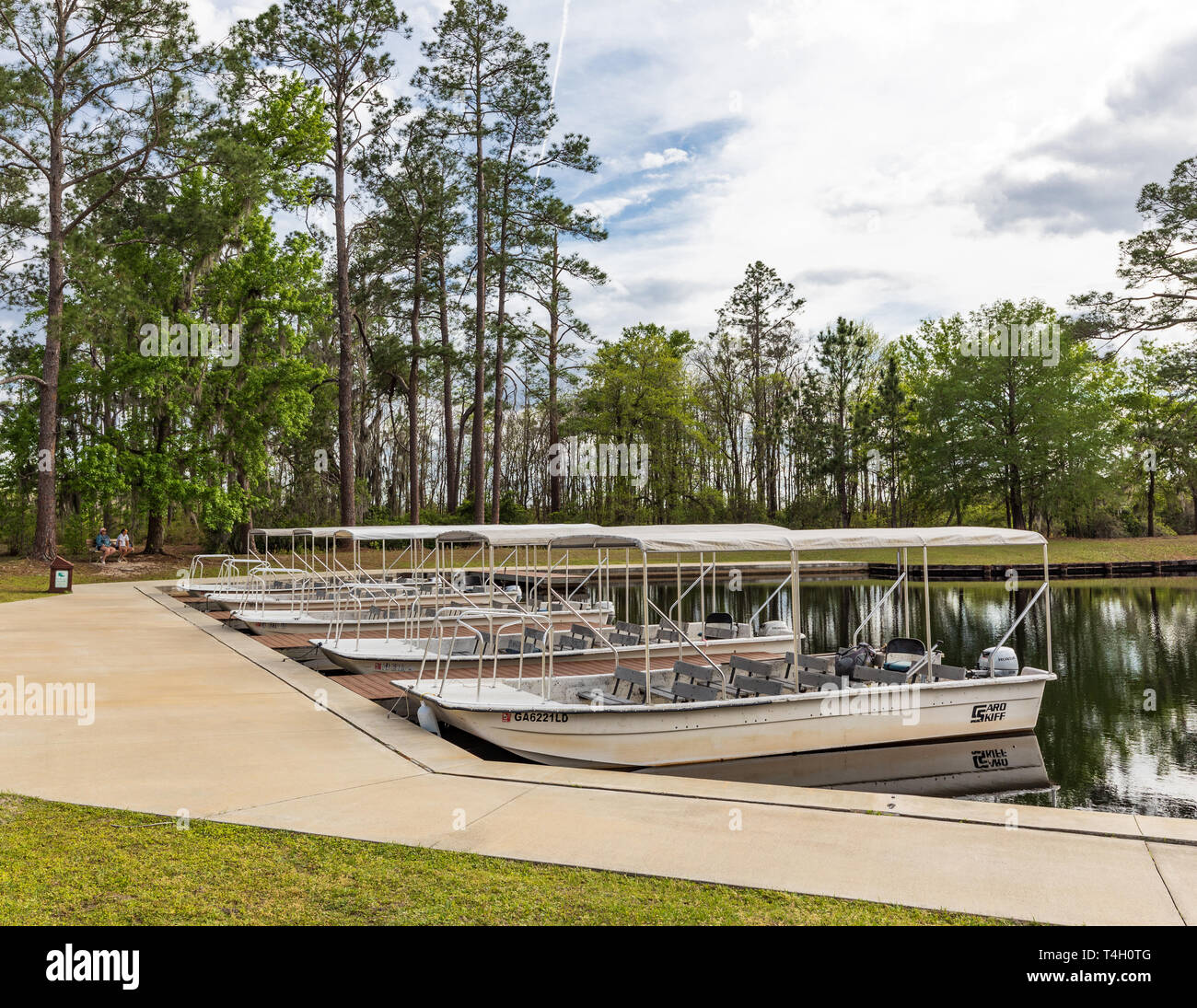 Okefenokee Swamp, Folkston, GA, USA-3/29/19: The canal at eastern entrance to the swamp, with skiffs at dock, and two women in background. Stock Photo