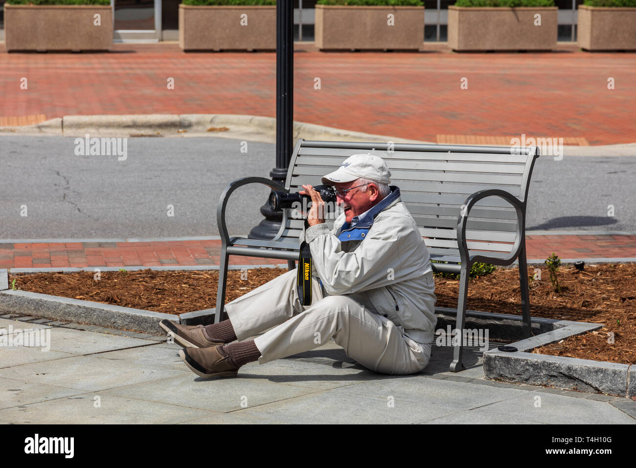ASHEVILLE, NC, USA-4/11/19:  A senior man sitting on the ground in front of a bench taking pictures with Nikon camera, and smiling. Stock Photo