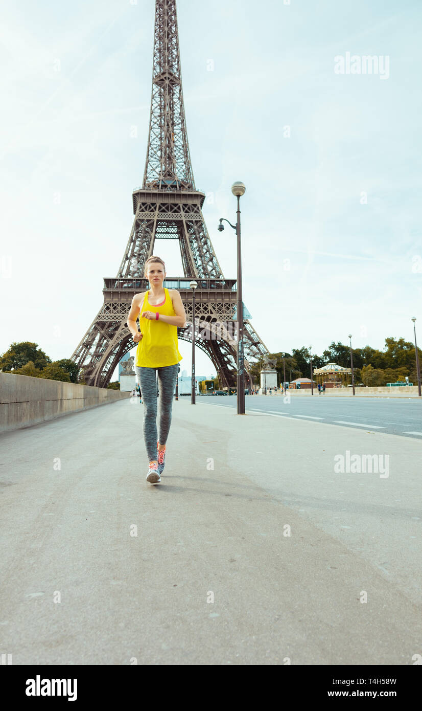 healthy woman in fitness clothes jogging against clear view of the Eiffel Tower in Paris, France. - Stock Image