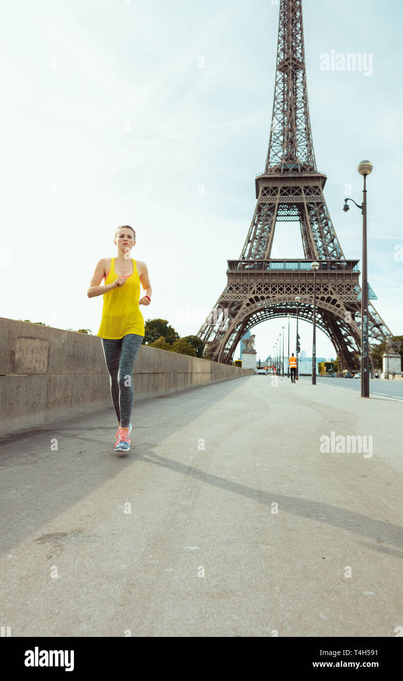 fit woman in fitness clothes in Paris, France jogging. - Stock Image
