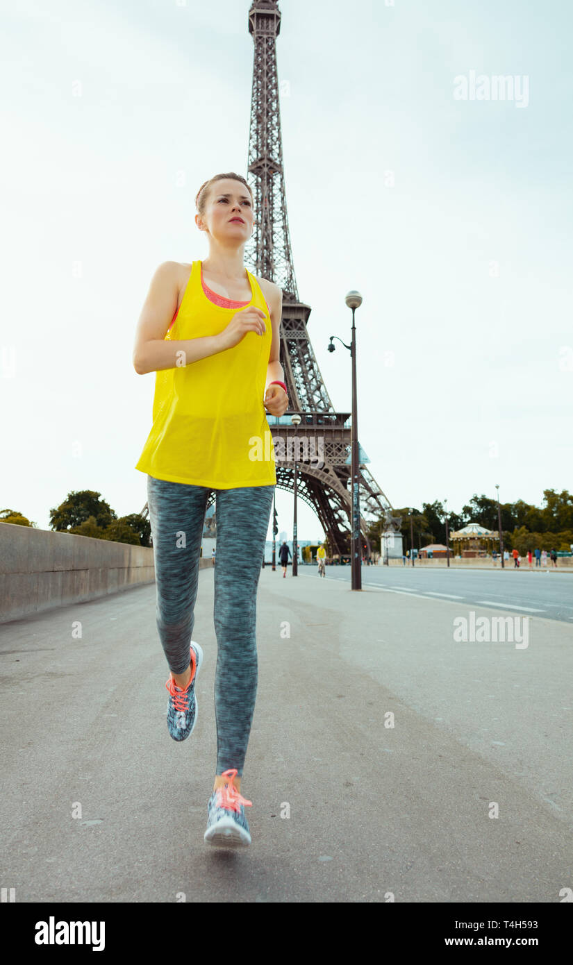 fit woman in fitness clothes in the front of Eiffel tower in Paris, France running. - Stock Image