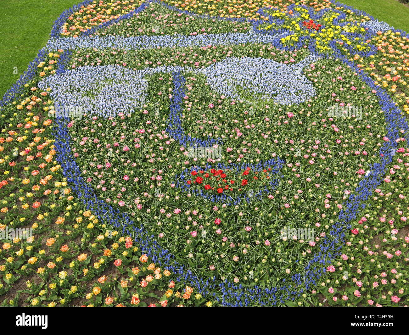 A flower bed display of planted bulbs featuring the visage of John Lennon in glasses for the 'Flower Power' theme at the 2019 Keukenhof tulip festival - Stock Image