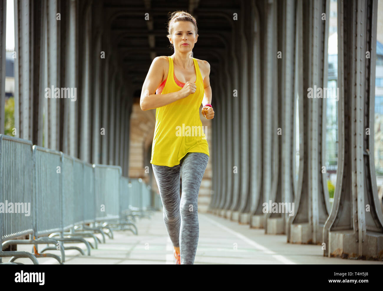 fit woman in fitness clothes on Pont de Bir-Hakeim bridge in Paris running. - Stock Image