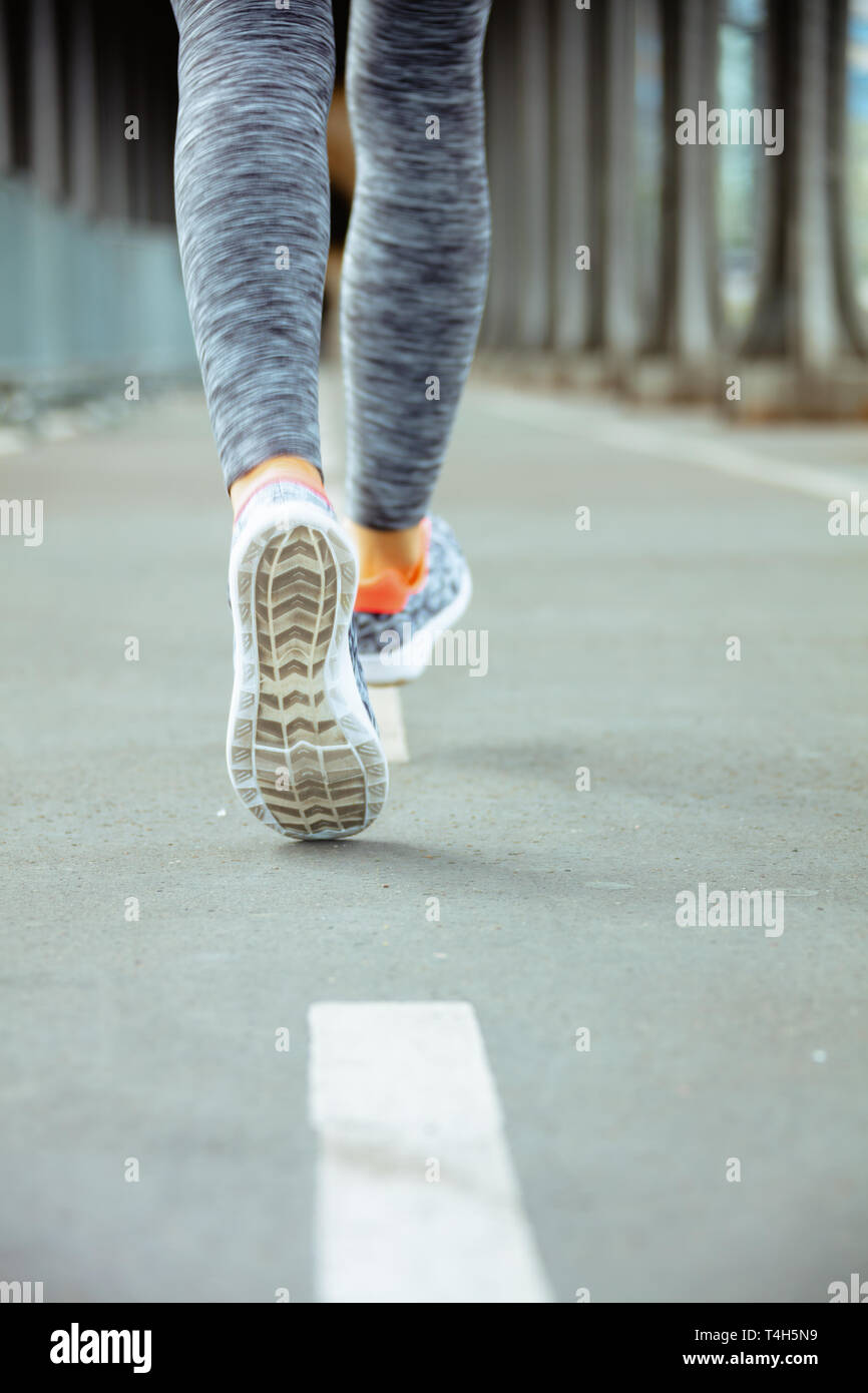 Closeup on healthy woman in fitness clothes on Pont de Bir-Hakeim bridge in Paris running. - Stock Image
