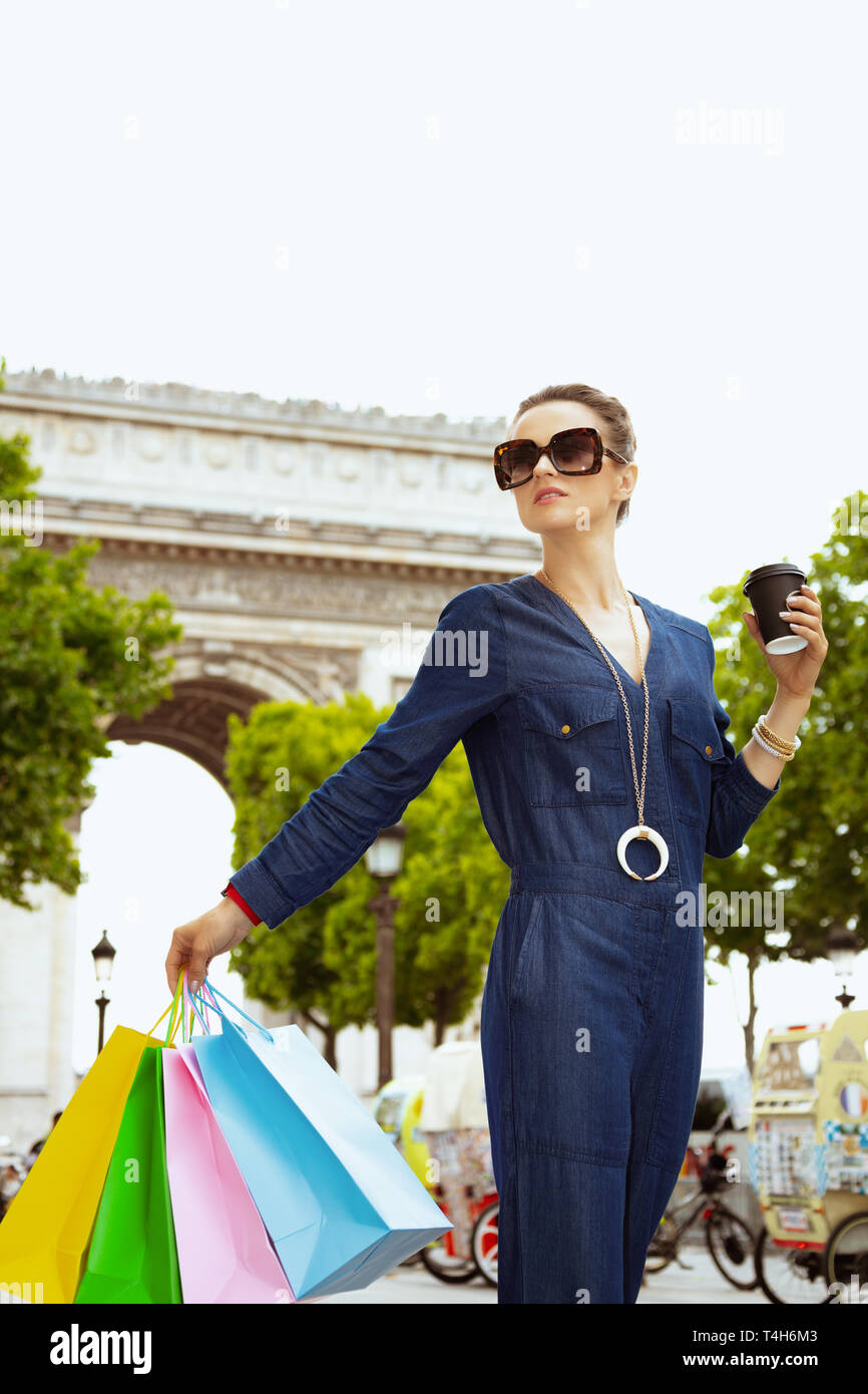 smiling young shopper woman in sunglasses with colorful shopping bags and cup of soy latte looking into the distance in Paris, France. - Stock Image