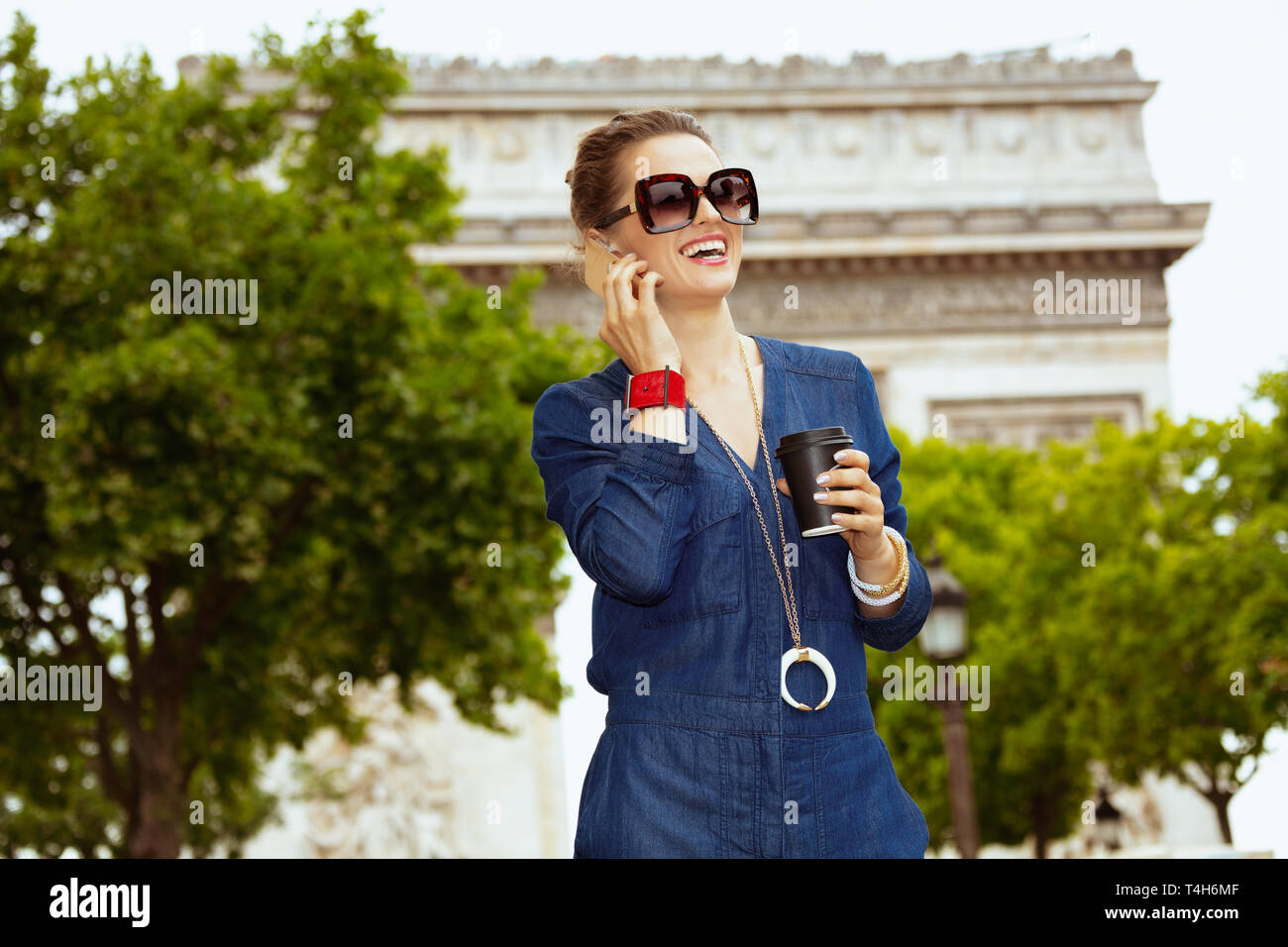smiling elegant solo traveller woman in sunglasses with coffee cup using a smartphone in Paris, France. Stock Photo
