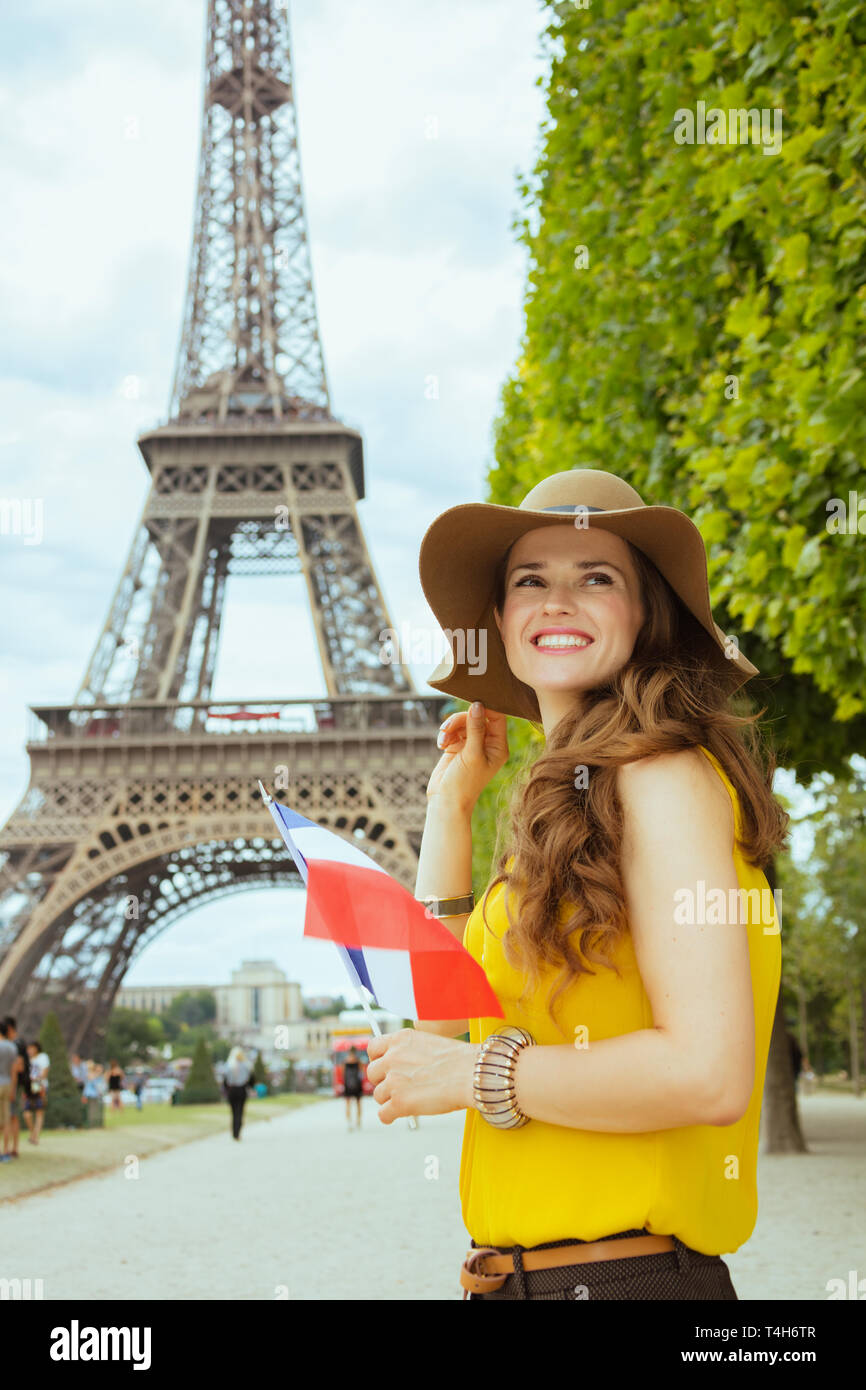 smiling elegant solo traveller woman in yellow blouse and hat with French flag looking into the distance in Paris, France. - Stock Image