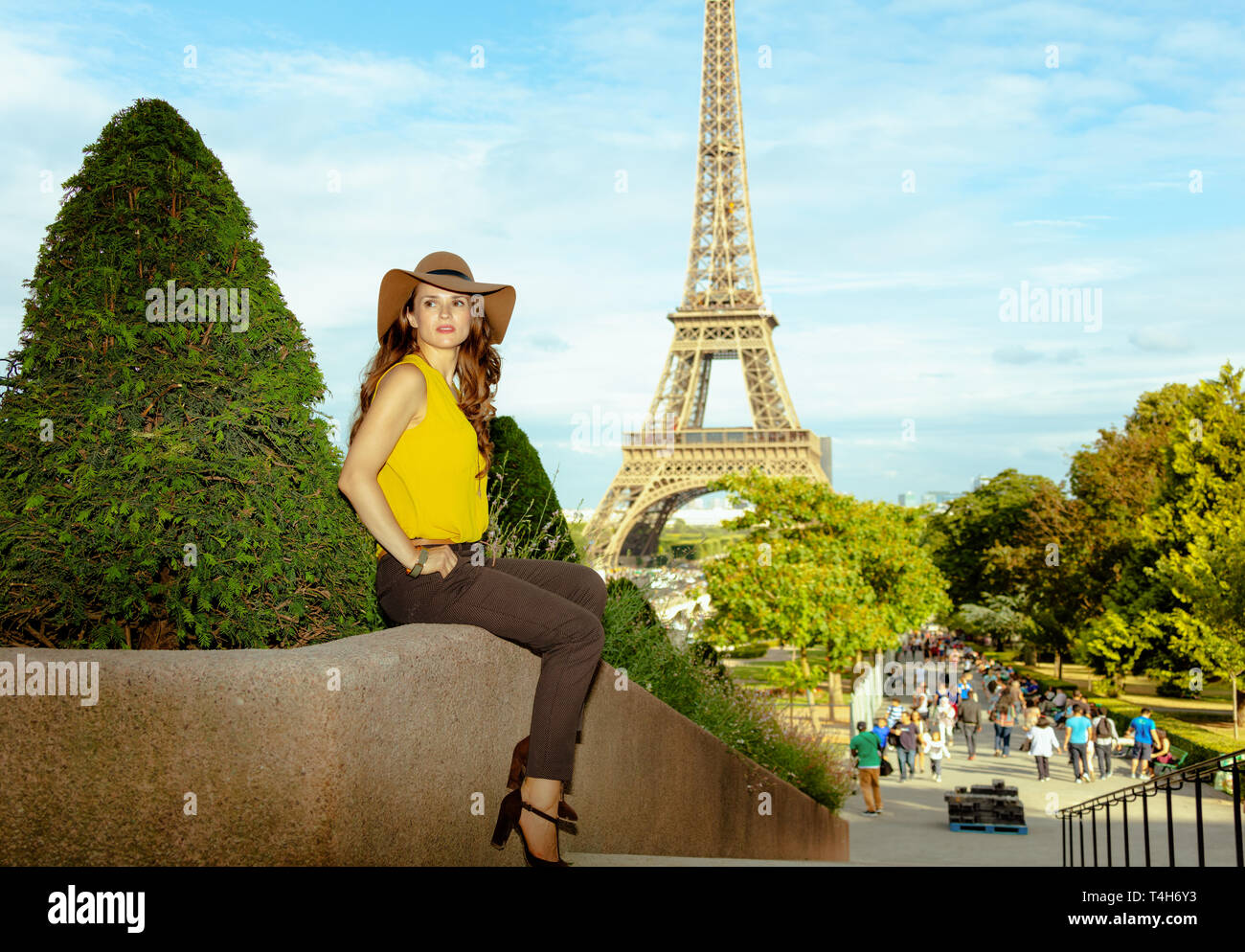 Full length portrait of pensive modern woman in yellow blouse and hat not far from Eiffel tower in Paris, France looking into the distance while sitti - Stock Image