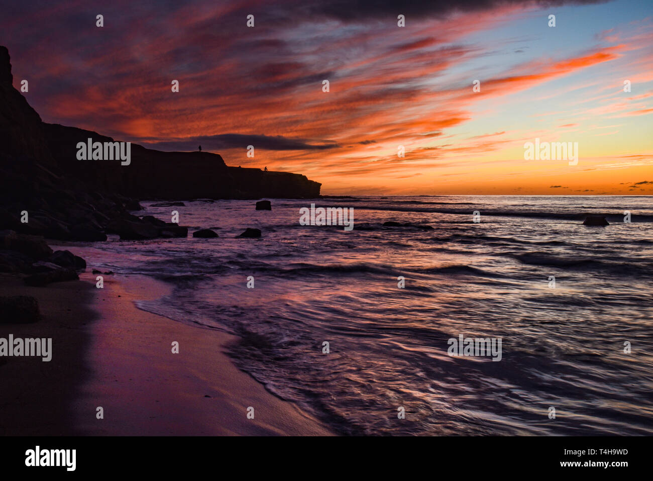 Spectacular, peaceful sunset at low tide, waves breaking over rocks, bright sky reflecting into water, Sunset Cliffs Natural Park, San Diego, CA, USA Stock Photo