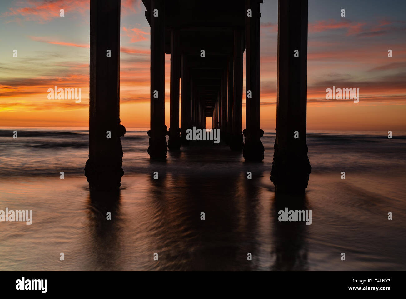 Brilliant sunset with drifting colorful clouds with a silhouette of the cement Scripps Pier with the tide coming in, La Jolla, San Diego, CA, USA. Stock Photo