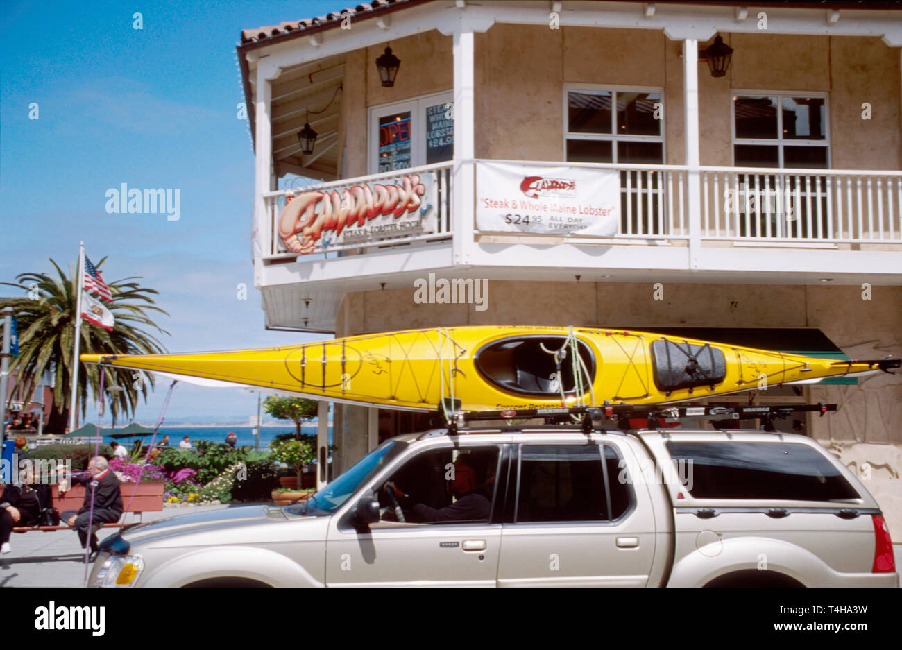 California Monterey Cannery Row Steinbeck Plaza stores kayak on vehicle - Stock Image