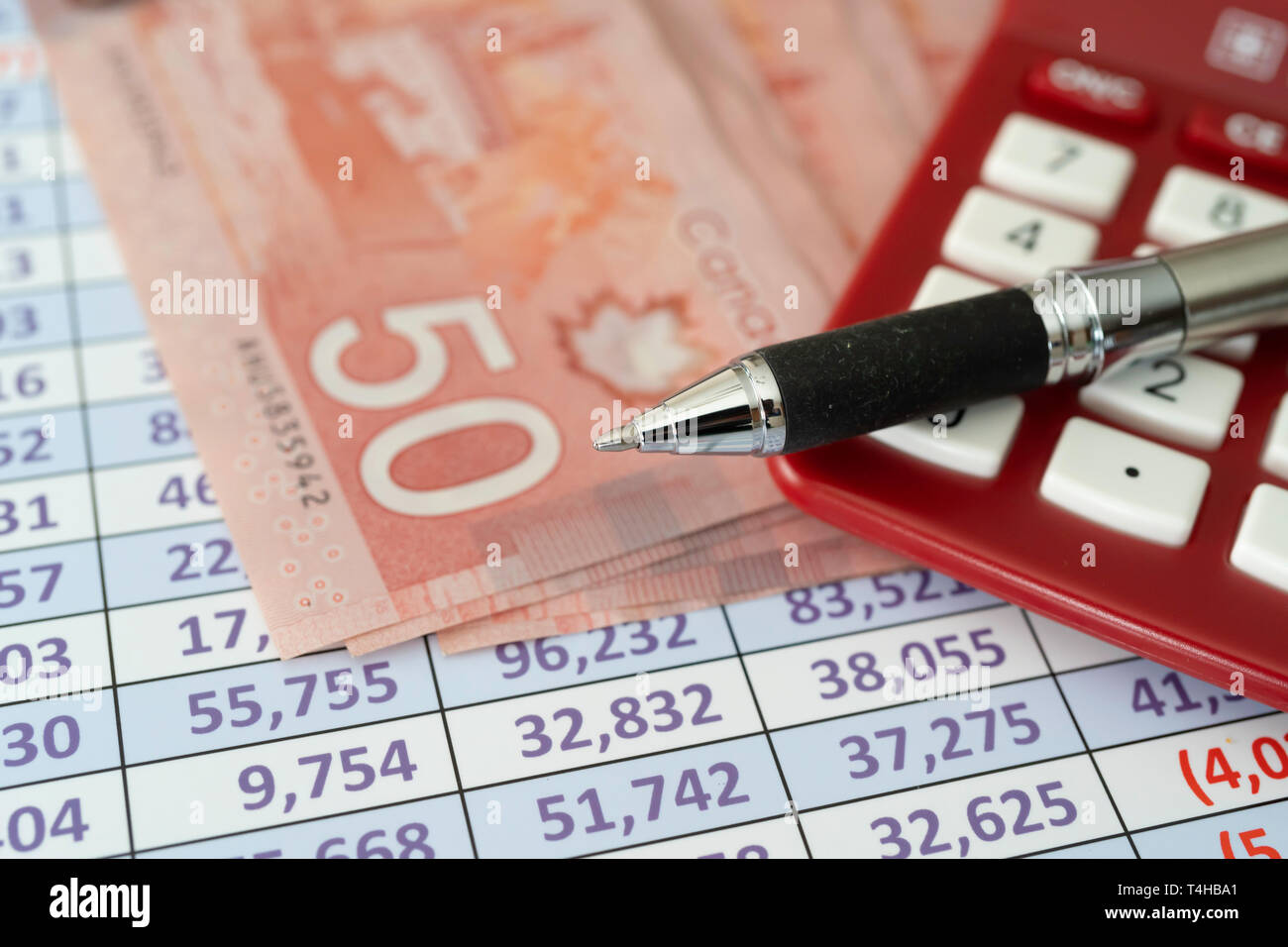Canadian Dollar Notes on spreadsheet with Calculator with pen - Stock Image
