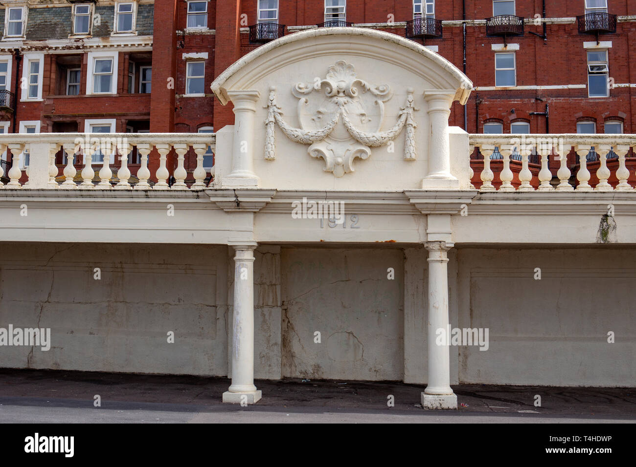 Seaside shelter under Metropole Hotel parking lot with removed seats dated 1912 in Blackpool Lancashire UK - Stock Image