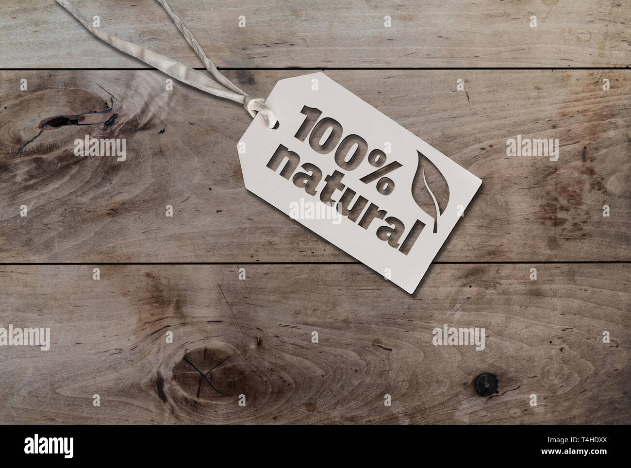 white hang tag cardboard lable with string attached an text 100% natural on rustic wooden table - Stock Image