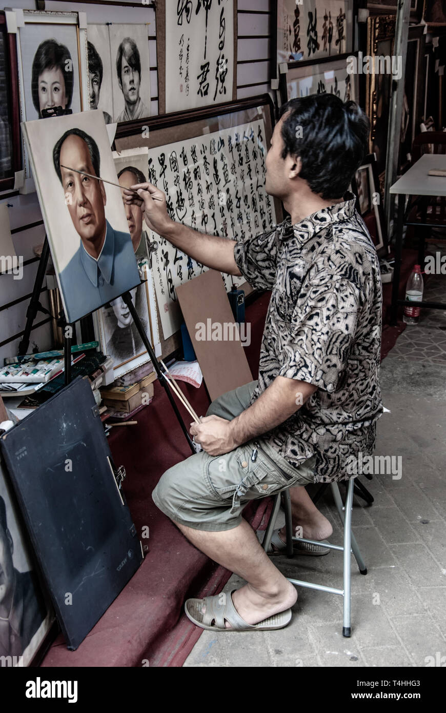 Artist paints vintage portrait of Mao. Chinese man of the Dafen Village at work. Residents specialize in copying and replicas of famous oil paintings. Stock Photo