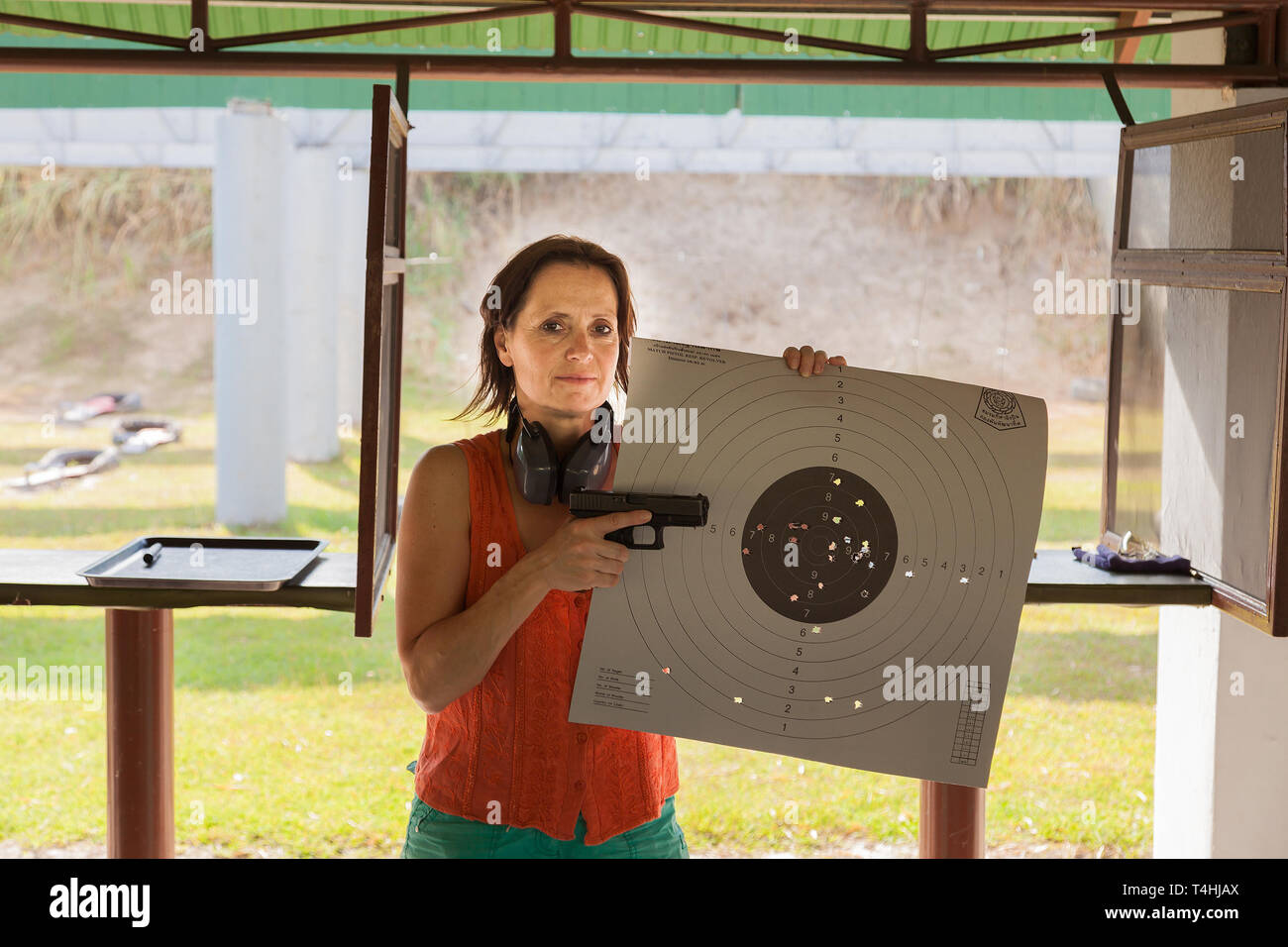 A woman at a shooting range with gun and target - Stock Image