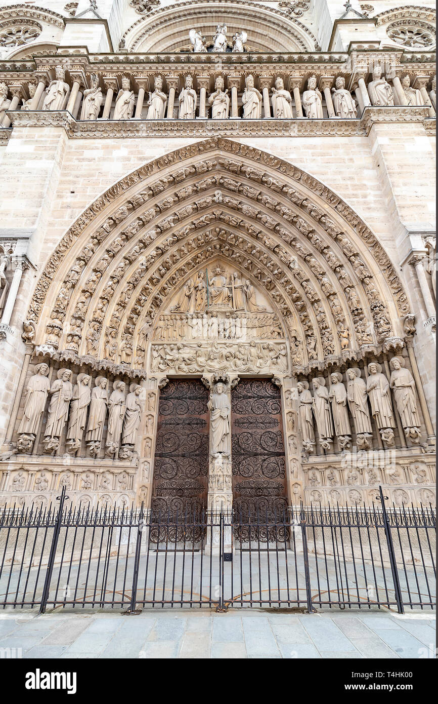 Main Entrance door of  Notre Dame Cathedral in Paris. Ornate Facade with sculptures statues and gargoyles. France - Stock Image