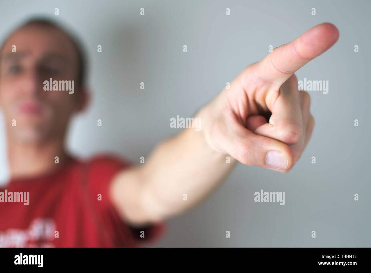 A man pointing away from the camera, as if sending someone away. - Stock Image
