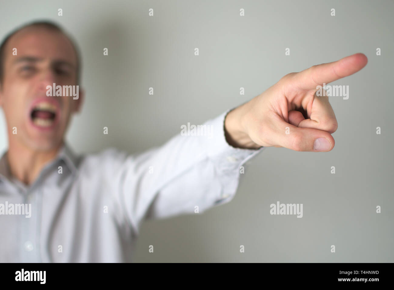 An angry man pointing away, as if firing someone. - Stock Image