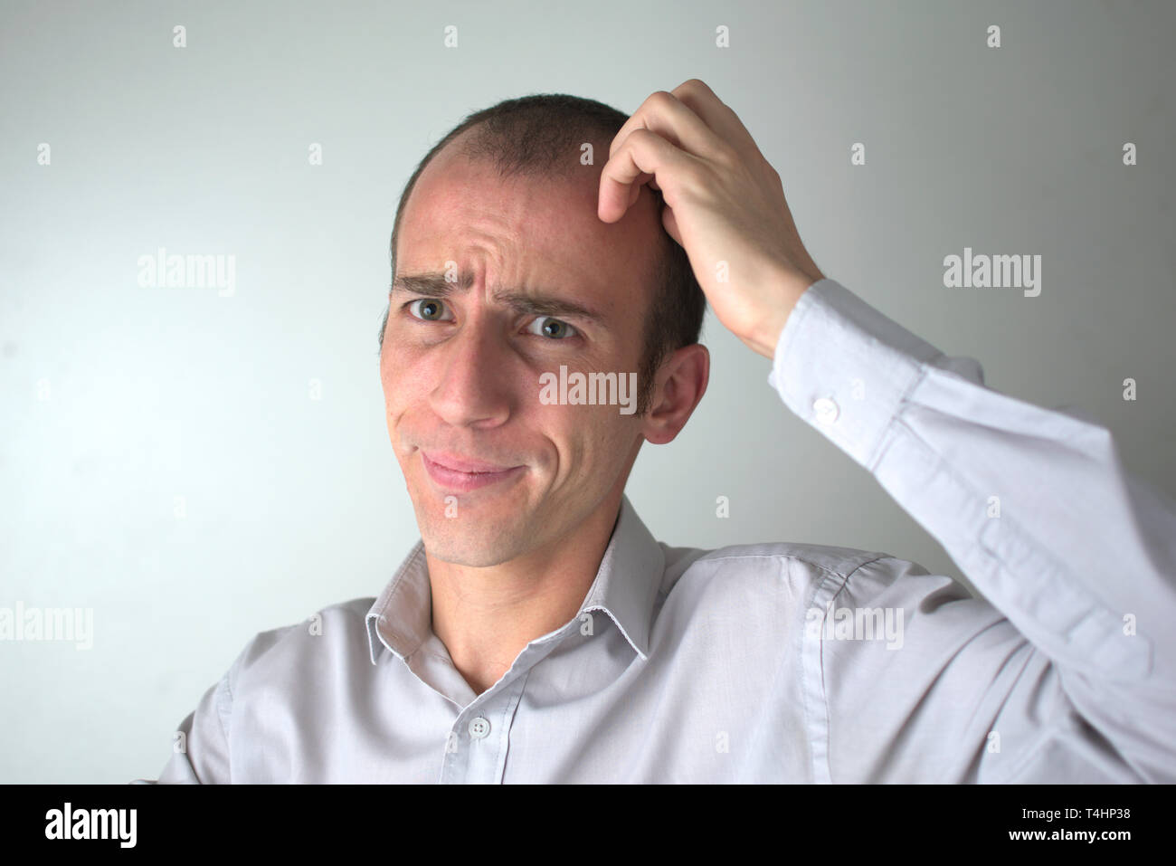 Studio shot of a business man with a troubled expression in his face. - Stock Image