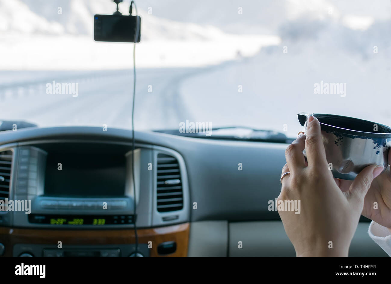 the hand of the girl in the passenger seat of the car holding hot tea from the mug from the thermos, view of the mountain winter road outside the car - Stock Image