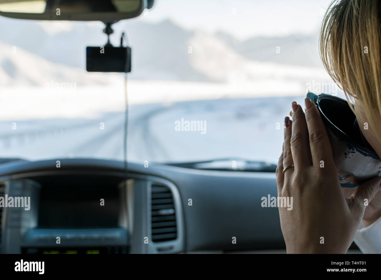 The girl in the passenger seat of the car drinking hot tea from a mug of a thermos, looking on the mountain winter road outside the car window - Stock Image