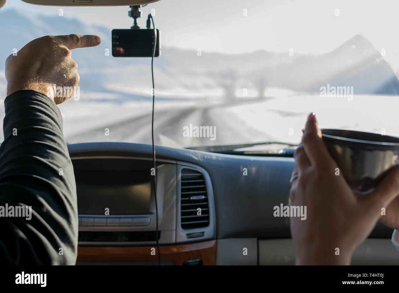 The hand of a man, the driver, shows the girl with a mug of tea, the direction of the road, in winter, in the snow-covered mountain area - Stock Image