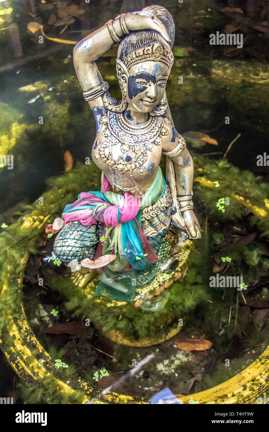 Religious statue at fountain, Thailand. Mother Earth Squeezing Her Hair. - Stock Image