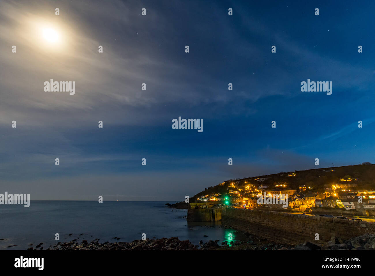 Mousehole, Cornwall, UK. 16th April 2019. UK Weather. After a day of sunshine, clear skies in the evening revealing the nearly full moon over the harbour town of Mousehole. Credit: Simon Maycock/Alamy Live News Stock Photo