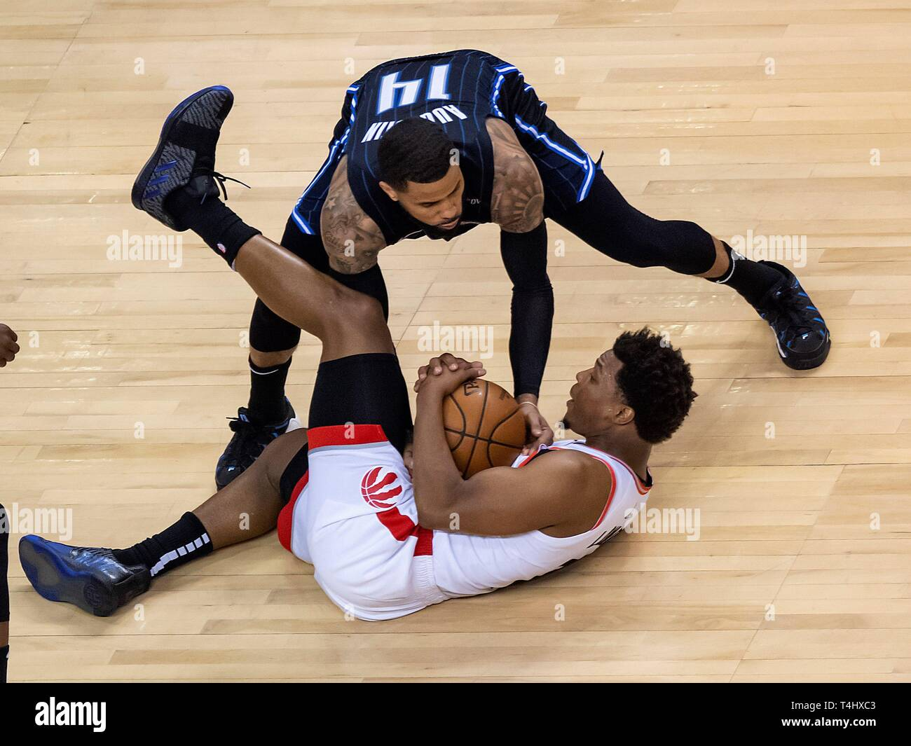 Toronto, Canada. 16th Apr, 2019. Orlando Magic guard D.J. Augustin (top) fights for possession of the ball against Toronto Raptors guard Kyle Lowry during the second quarter of game two in their NBA Eastern Conference Quarterfinals basketball game at Scotiabank Arena in Toronto, Canada, 16 April 2019. Credit: Warren Toda/EFE/Alamy Live News - Stock Image