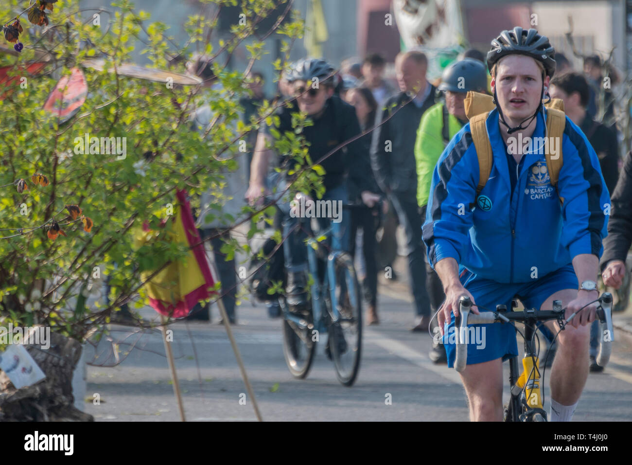London, UK. 17th Apr 2019. Commuters have the unusal experience of passing the newly greened bridge - Morning on Waterloo Bridge sees the camp awake and commuters make their progress on foot and bike across the river - Day 3 - Protestors from Extinction Rebellion block several junctions in London as part of their ongoing protest to demand action by the UK Government on the 'climate chrisis'. The action is part of an international co-ordinated protest. Credit: Guy Bell/Alamy Live News Stock Photo