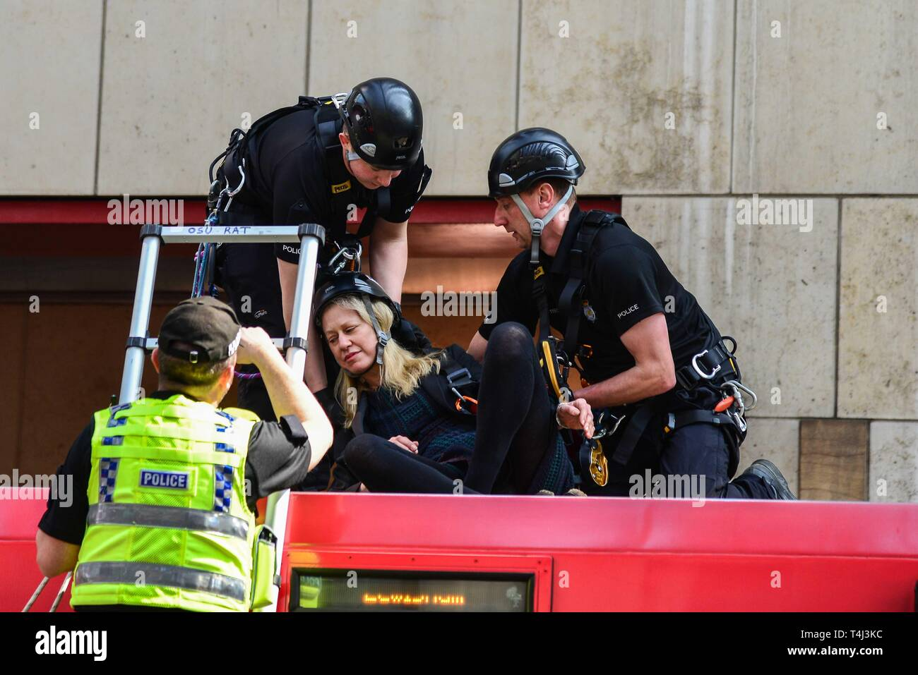 London, UK. 17th Apr, 2019. Police officers place a protester who glued herself to the roof of a DLR train carriage into a safety harness at Canary Wharf station in London, UK on April 17, 2019. This is part of on going climate change protests in London. Credit: Claire Dohert/Alamy Live News Stock Photo