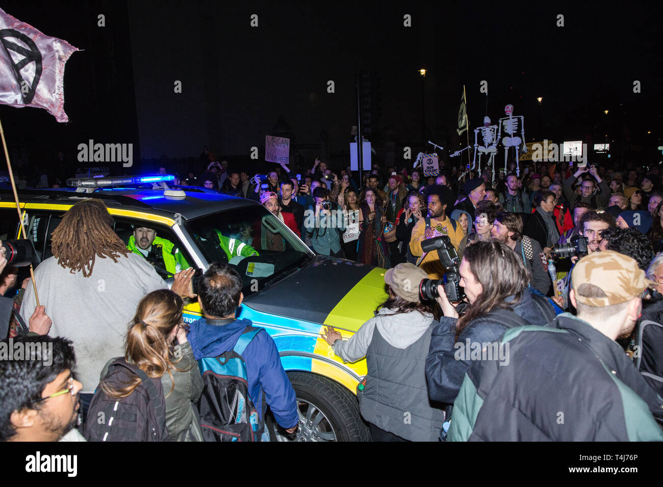 London, UK. 17th April 2019. A police vehicle is briefly trapped among drummers from climate change action movement Extinction Rebellion marching towards Westminster Bridge from Parliament Square during a police operation to clear protesters taking part in the International Rebellion in order to reopen the square to traffic.  Credit: Mark Kerrison/Alamy Live News - Stock Image