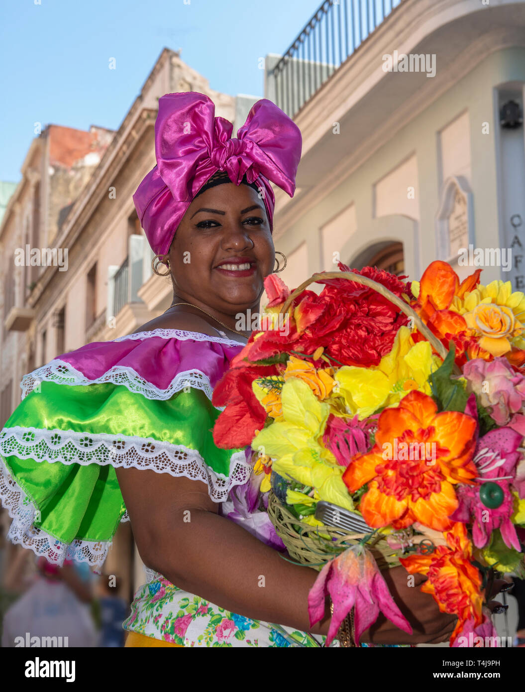 Cuban woman with traditional floral  clothing posing for tourists in street in  Old Havana, Cuba Stock Photo