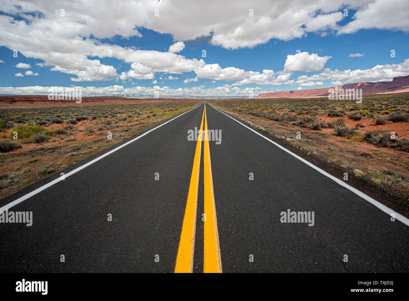 White clouds above an empty road on the northern Arizona Highway 89. - Stock Image